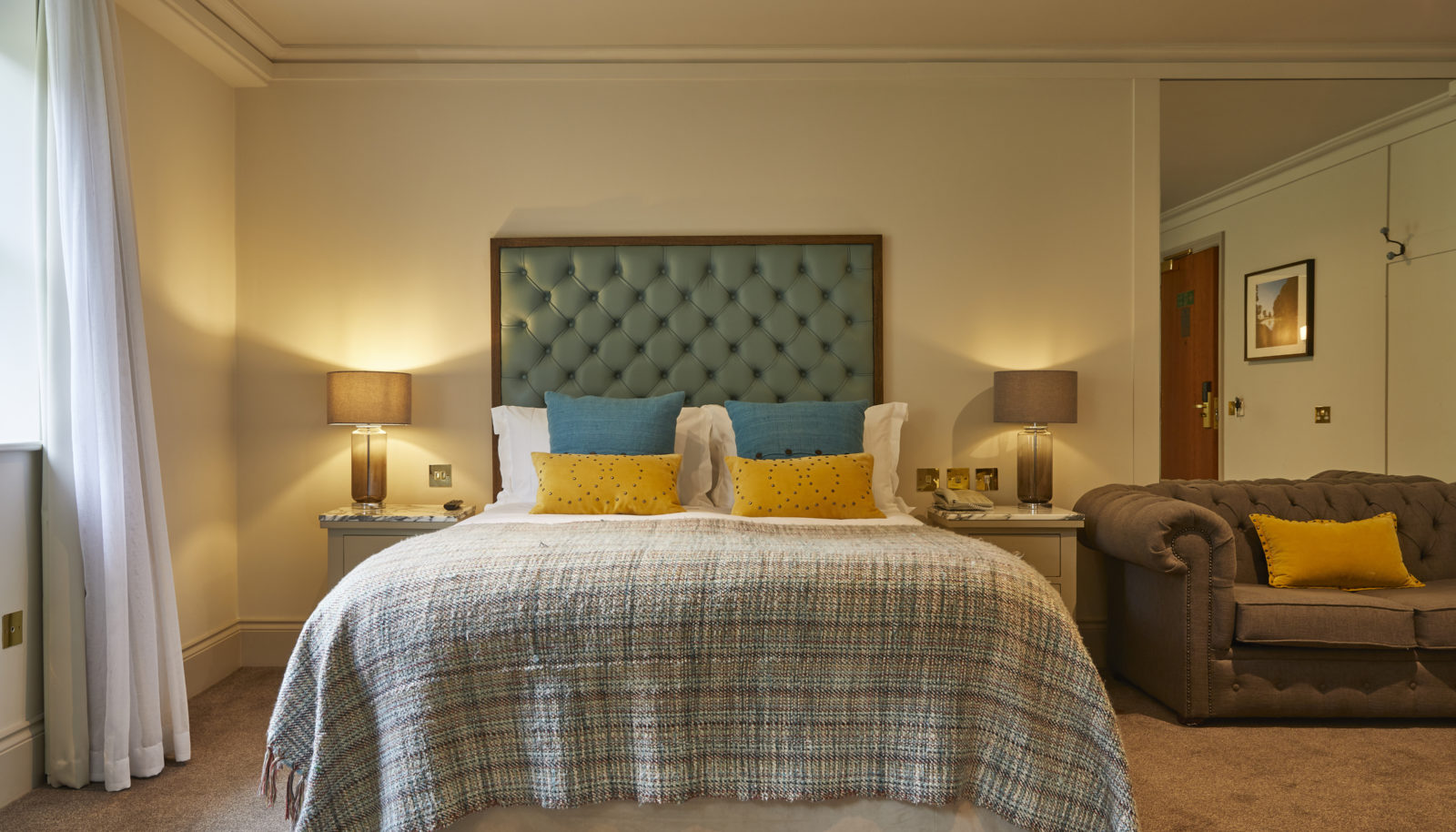 Relaxed double room bed with teal headboard and sofa
