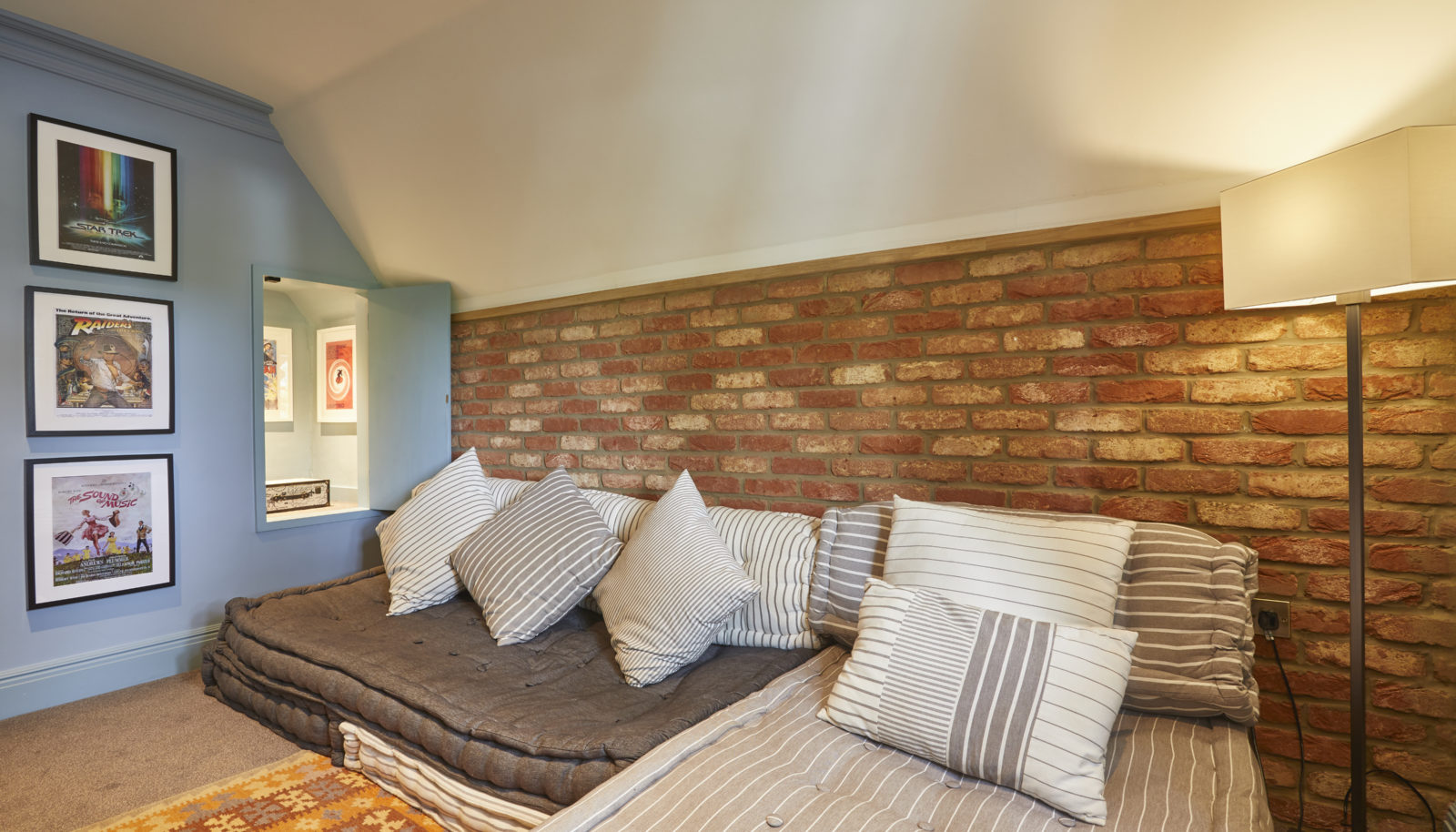 Coach house room with floor cushions seating area brick wall and blue walls with art
