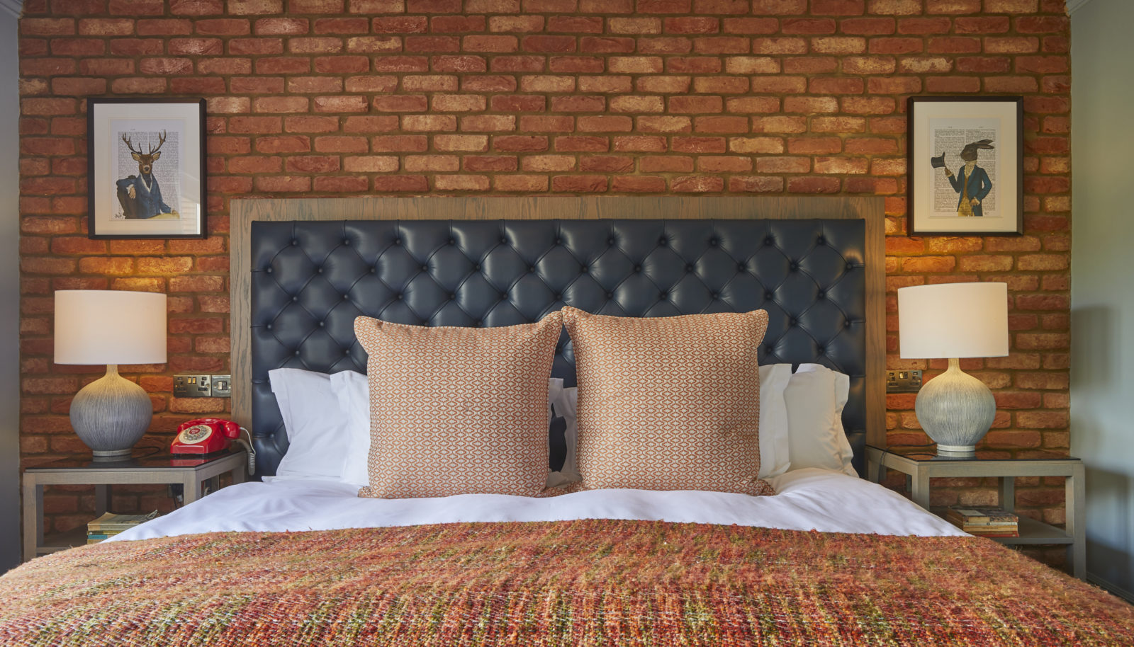 deluxe river view room with cushions on bed and brick wall and fun art