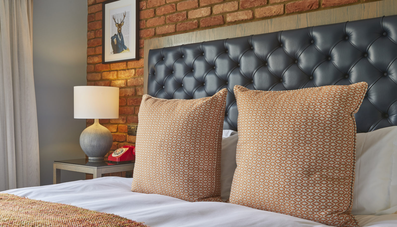Cushions on bed with brick wall and fun art