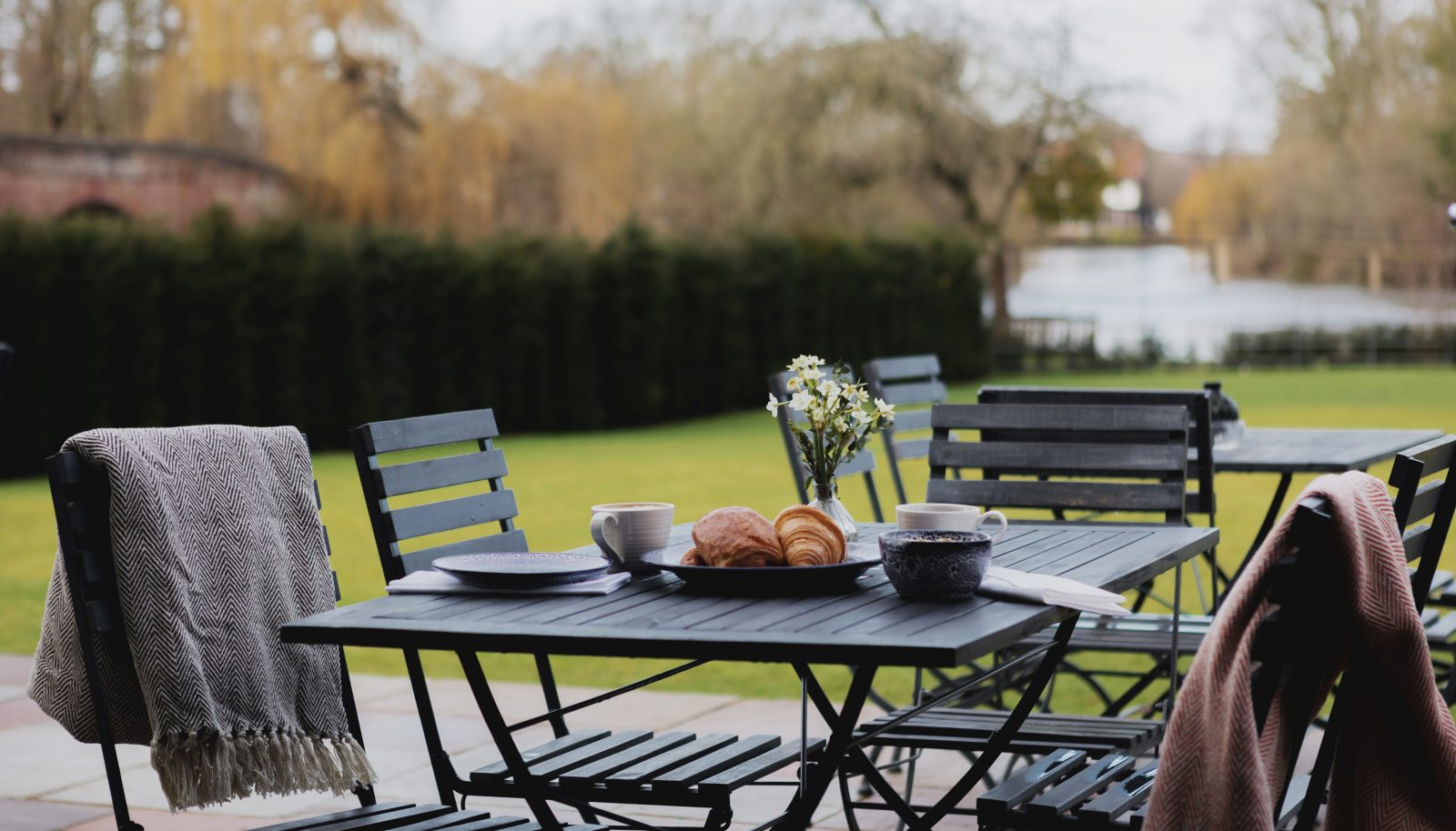 outdoor tables and chairs with breakfast pastries and coffee and blankets