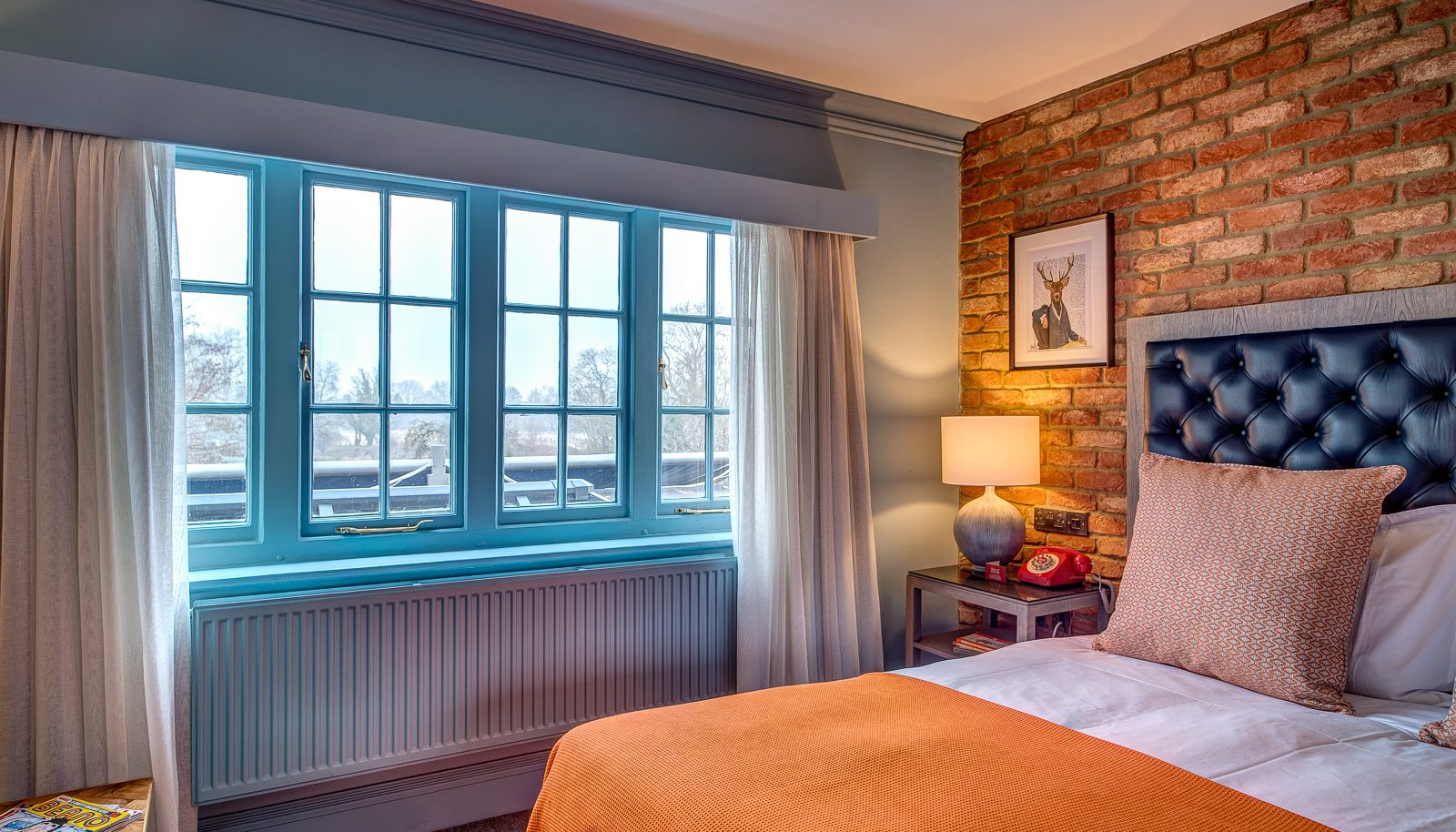 bedroom with brick wall and blue windows river view