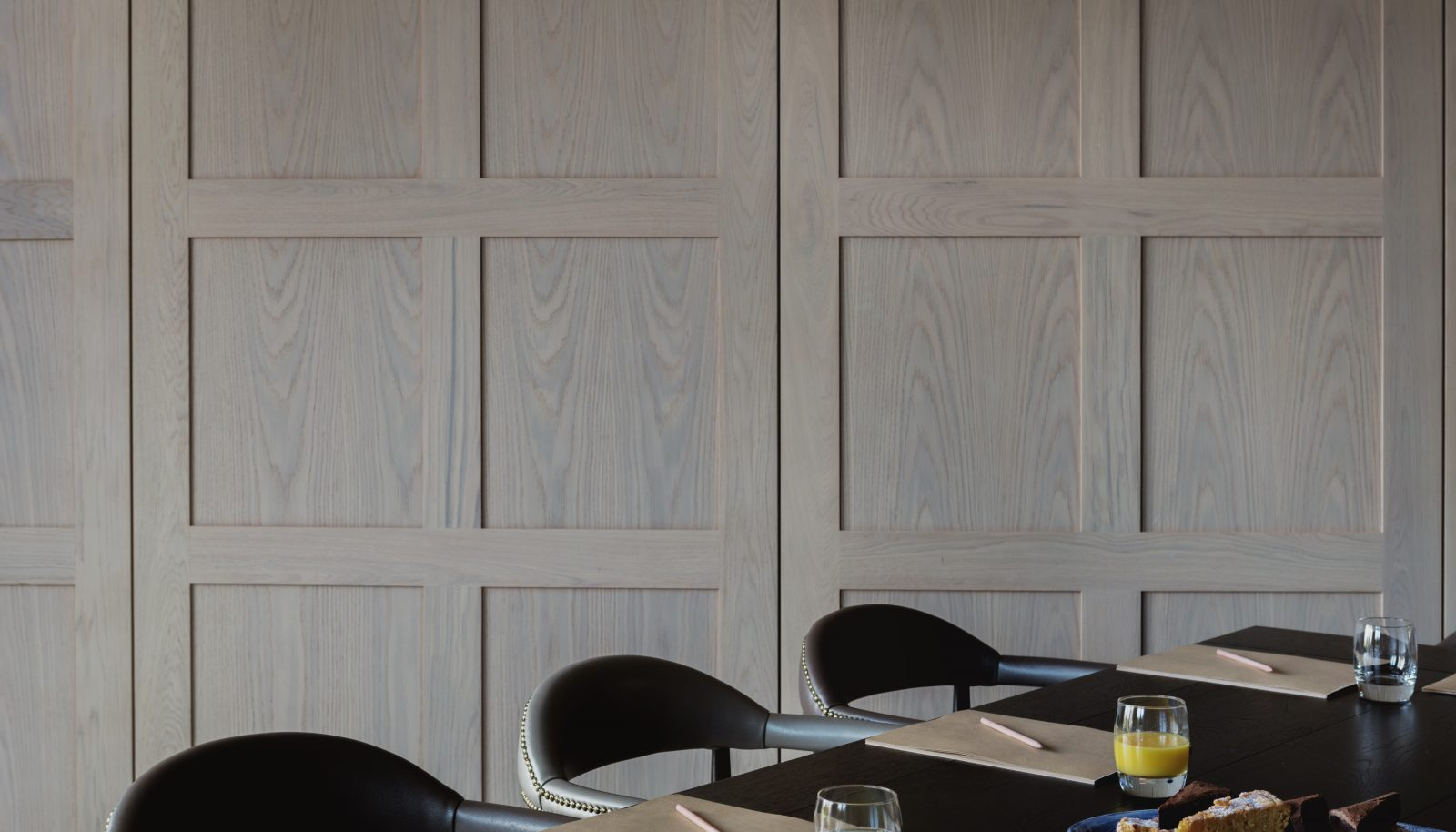 paneled wall in boardroom with notepads and breakfast