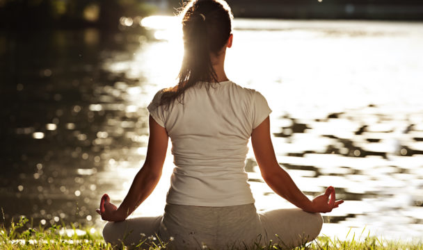 woman relaxing yoga by the river in the sunshine
